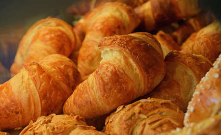 bakery store: Freshly baked golden brown French croissants in retail bakery store display, close up, high angle view