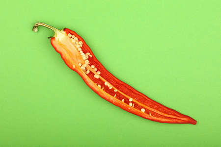 One cut half of fresh red hot chili pepper on green paper background, close up, elevated top view