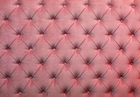 Pink velvet capitone textile background, retro Chesterfield style checkered soft tufted fabric furniture diamond pattern decoration with buttons, close up