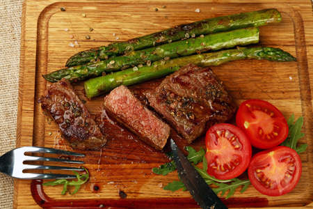 Cut slices of grilled juicy medium cooked beefsteak served on wooden board with fresh green rocket salad, asparagus and red cherry tomatoes, fork and knife, close up, high angle view