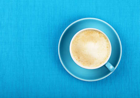 Full cup of latte cappuccino coffee with milk froth on saucer over blue tablecloth, close up, elevated top view
