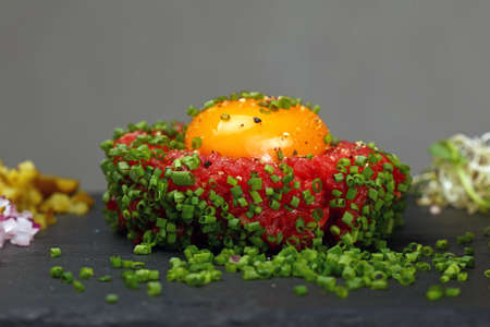 One portion of raw minced beef meat tartare steak with egg yolk ant green shallot onions served on black slate board, close up, low angle side view Stock Photo
