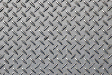 diamond plate: Gray industrial anti slip embossed metal steel plate with diagonal bumps of diamond pattern texture, background, close up Stock Photo
