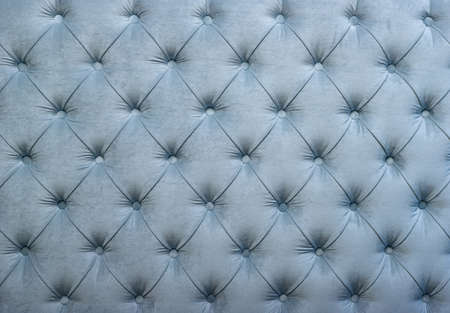 Light blue velvet capitone textile background, retro Chesterfield style checkered soft tufted fabric furniture diamond pattern decoration with buttons, close up
