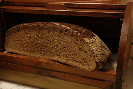 Half of artisan dark black fresh rye bread loaf in traditional rustic vintage wooden breadbin box, close up, low angle view