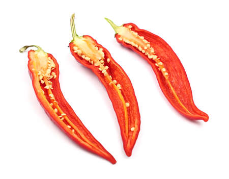close up food: Three cut halves of fresh red hot chili peppers isolated on white background, close up, high angle view