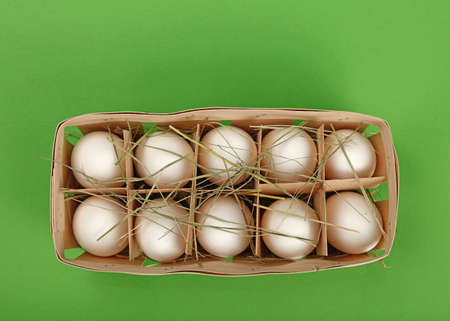 close up food: Ten fresh white farm chicken eggs in wooden container box with hay over green background, elevated top view, directly above Stock Photo