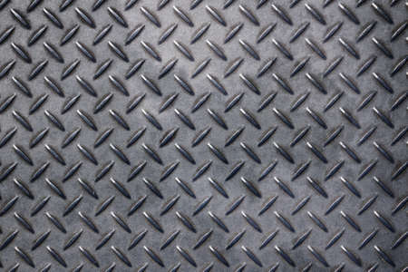 rivets: Dark gray grunge industrial anti slip embossed metal steel plate with diagonal bumps of diamond pattern texture, background, close up