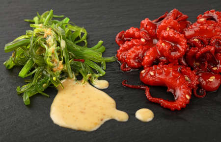 Seafood small whole red baby octopus salad with green seaweeds and peanut sauce on black slate board, close up, high angle view Stock Photo