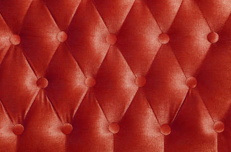 Scarlet ruby red capitone textile background with buttons, retro Chesterfield style soft tufted fabric furniture upholstery diamond pattern decoration, close up Stock Photo