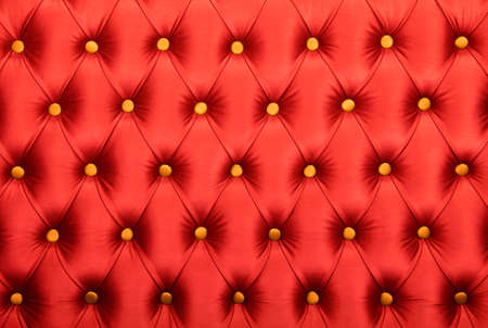 button tufted: Scarlet ruby red capitone textile background with golden yellow buttons, retro Chesterfield style soft tufted fabric furniture upholstery diamond pattern decoration, close up