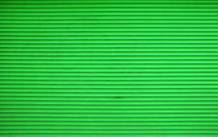 Vivid green painted horizontal metal window roller shutter blinds or garage doors background texture
