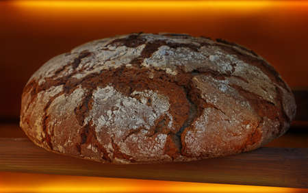 Whole round loaf of fresh artisan black rye bread with brown crust, fresh out of oven, close up, low angle view