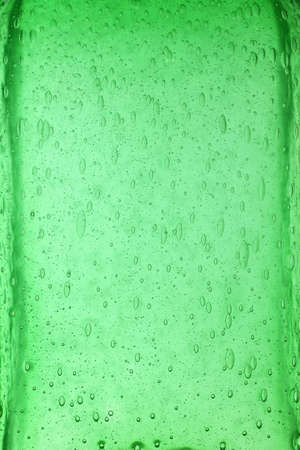 Background texture of solid transparent green color glass with pattern of air bubbles, close up