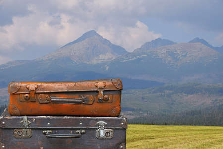 Stack of two old vintage antique grunge travel luggage brown leather suitcase trunks over background of mountain landscape, close up, low angle side view Stock Photo