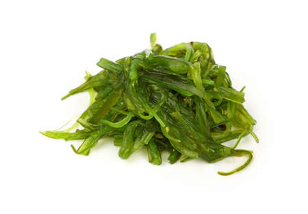 Close up portion of green wakame seaweed salad isolated on white background, high angle view Banco de Imagens