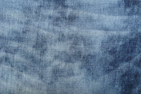 Dark indigo blue cotton jeans denim texture background with light washed distressed faded area, close up