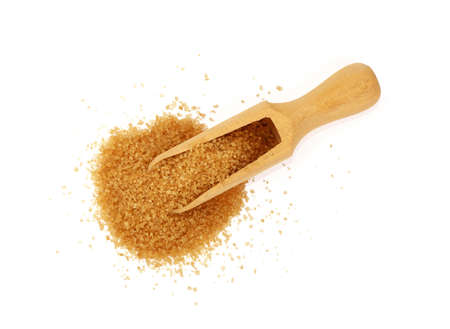 Close up one wooden scoop spoon full of raw brown cane sugar with pinch spilled and spread around, isolated on white background, elevated top view, directly above