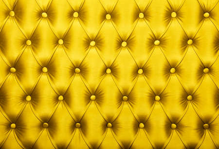 Yellow vivid capitone textile background, retro Chesterfield style checkered soft tufted fabric furniture diamond pattern decoration with buttons, close up Stock Photo