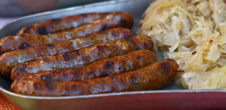 Close up portion of grilled Nuremberg Bratwurst sausages with side dish of sauerkraut on metal pewter plate, low angle view