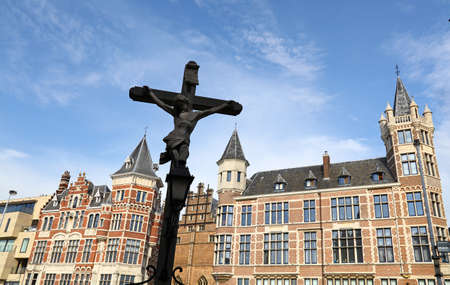 Low angle view of cross rood over old historical buildings and clear blue sky of Antwerp, Belgium Stock Photo