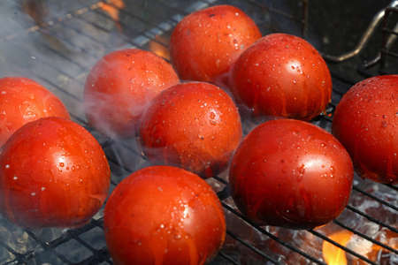 Red tomatoes cooked on fire barbecue grill with smoke and flame, close up, high angle view Stock Photo
