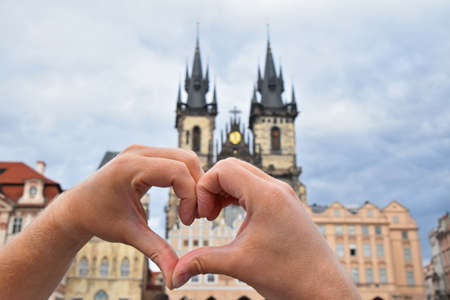Close up man hands showing heart shape love symbol over cityscape with Cathedral of Our Lady before Tyn, Prague, Czech Republic