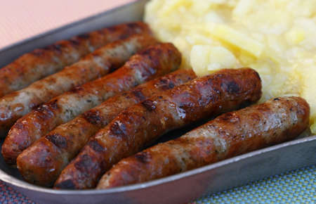 Close up portion of grilled Nuremberg Bratwurst sausages with side dish of potato salad on metal pewter plate, low angle view
