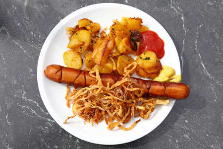 Close up portion of one big grilled sausage with homemade roasted potato, fried onion rings, ketchup and mustard on white plate over grey table, elevated top view, directly above