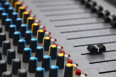 Close up audio control sound mixing console board with fader bars, buttons and sliders, high angle view