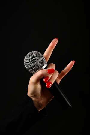Woman hand with red nails holding microphone with devil horns rock metal sign isolated on black background