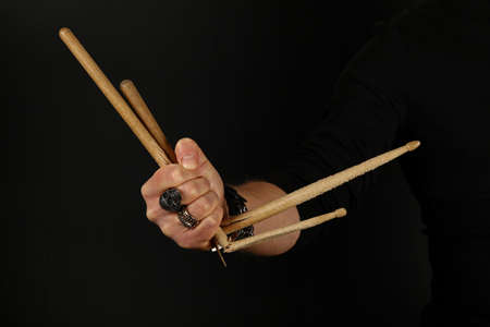 Close up man hand holding two broken drumsticks over black background, side view