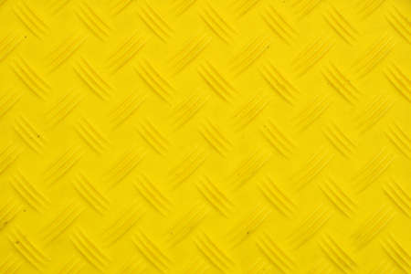 Vivid yellow industrial anti slip embossed plastic plate with diagonal bumps of diamond pattern texture, background, close up