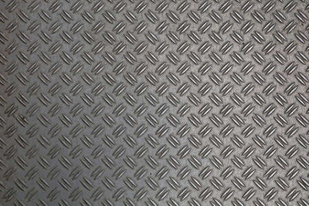 Dark gray industrial anti slip embossed metal steel plate with double diagonal bumps of diamond pattern texture, background, close up