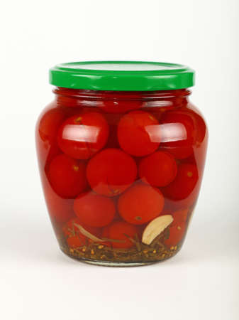 Close up of one glass jar of pickled small red cherry tomatoes with green lid over white background, low angle side view