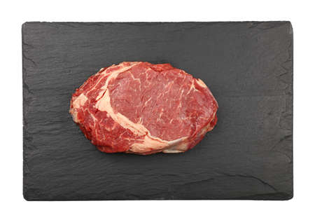 Close up one raw ribeye beef steak on black slate board isolated on white background, elevated top view, directly above Stock Photo