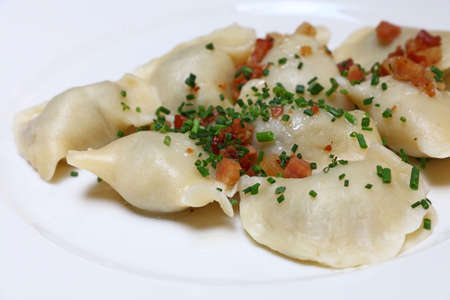 Plate of pierogi or varenyky stuffed filled dumplings with bacon crisps and green chive onion, traditional East Europe cuisine meal popular in Poland, Ukraine, Slovakia and Russia, close up, high angle view