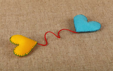 Felt craft and art, two handmade stitched toy hearts, yellow and blue, with red twine on canvas background, close up, high angle view