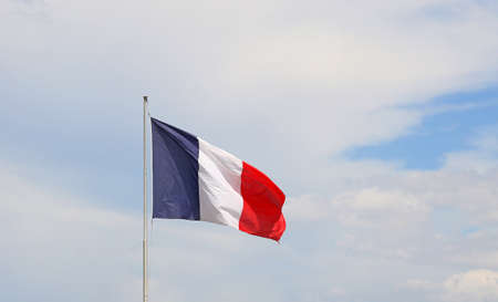 Close up flag of France waving and blowing in the wind over blue sky, low angle view Banco de Imagens