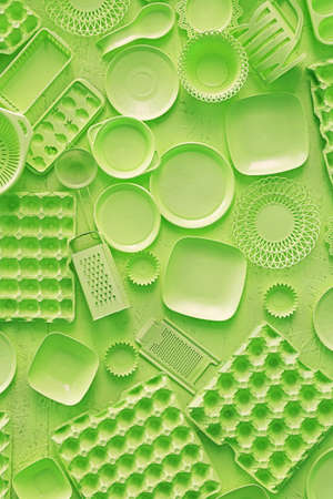 Close up flat lay of different green color painted kitchen utensils and tools, grater, spoon, egg carton, plastic disposable plates, elevated top view, directly above