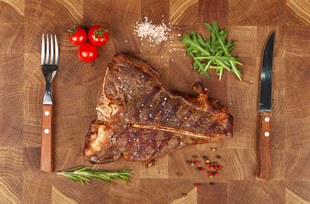 Close up one big grill roasted T-bone porterhouse beef steak with rib bone served on wooden cutting board, elevated top view, directly above
