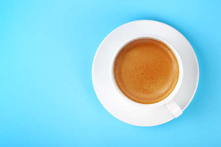 Close up one full white cup of espresso coffee and saucer over pastel blue paper background, elevated top view, directly above Фото со стока
