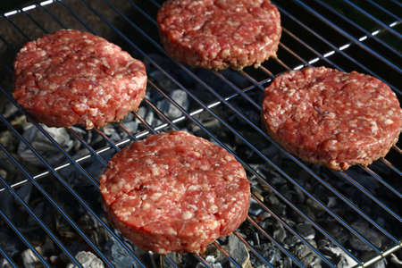 Close up raw beef or pork meat barbecue burgers for hamburger cooked grilled on bbq grill, high angle view Stock Photo