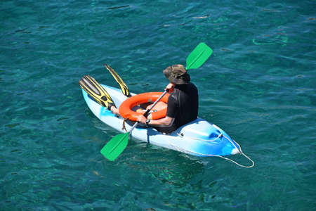 High angle view of one beach lifeguard man at kayak boat in blue sea water