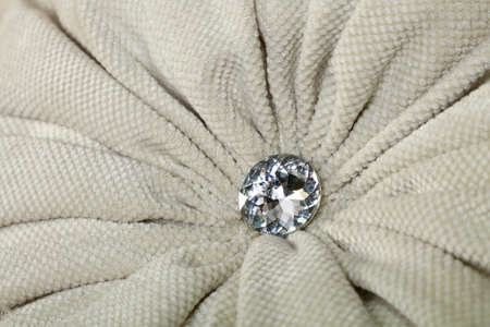 Close up diamond shaped crystal strass or rhinestone decoration on grey beige furniture textile upholstery Stock Photo