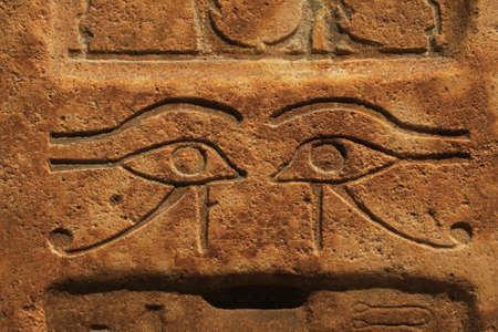 Zamknij się tło zabytkowej kamiennej ściany z rzeźbionymi starożytnymi egipskimi płaskorzeźbami wadjet, oko Ra lub Horusa, widok z przodu