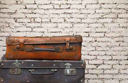 Close up stack of two old vintage antique grunge travel luggage brown leather suitcase trunks isolated over background of white brick wall, low angle side view Stock Photo