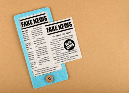 Close up felt craft blue smartphone with FAKE NEWS newspapers feed from screen over brown paper background, elevated top view, directly above