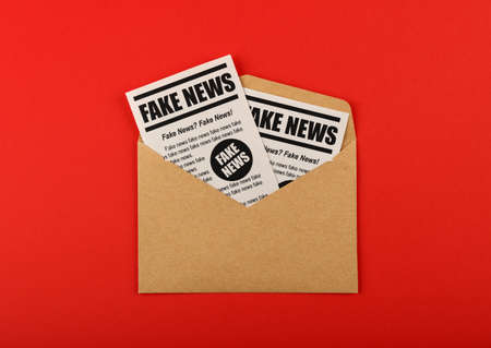 Close up brown paper mail envelope with FAKE NEWS newspapers over red background with copy space, elevated top view, directly above Foto de archivo