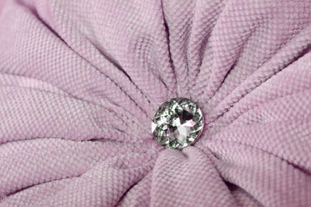 Close up diamond shaped crystal strass or rhinestone decoration on pastel pink furniture textile upholstery